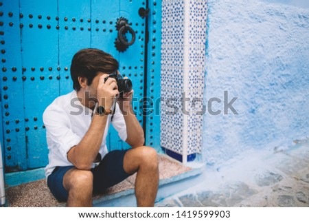 Hipster guy with retro equipment in hands taking rest near ancient blue door making photos of Unesco architecture buildings, man visit Morocco during summer vacations photographing historic center