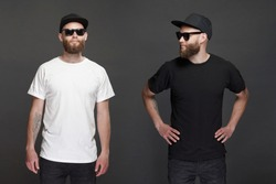 Hipster handsome male model with beard wearing black and white blank t-shirt and a baseball cap with space for your logo
