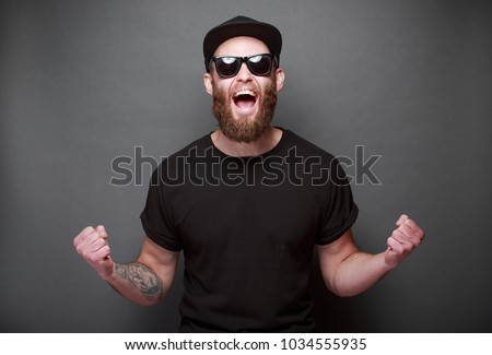 Hipster handsome male model with beard wearing black blank t-shirt with space for your logo or design over gray background #1034555935