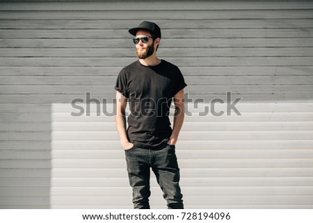 Hipster handsome male model with beard wearing black blank t-shirt with space for your logo or design in casual urban style #728194096