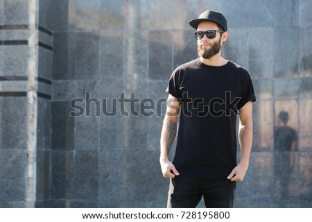 Hipster handsome male model with beard  wearing black blank  t-shirt with space for your logo or design in casual urban style #728195800