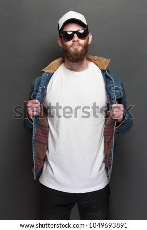 Hipster handsome male model with beard wearing white blank t-shirt and a baseball cap with space for your logo or design in casual urban style #1049693891