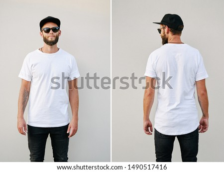 Hipster handsome male model with beard wearing white blank t-shirt and a baseball cap with space for your logo or design in casual urban style. Back and front view