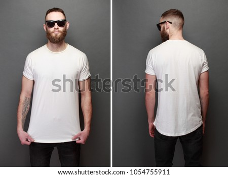 Hipster handsome male model with beard wearing white blank t-shirt with space for your logo or design over gray background #1054755911