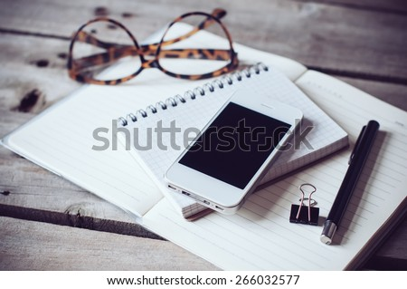 Hipster home office tabletop: papers and notebooks, reading glasses, smart phone, pen on an old wooden board background. Vintage lifestyle.