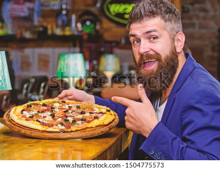 Hipster hungry eat italian pizza. Pizza favorite restaurant food. Fresh hot pizza for dinner. Hipster client sit at bar counter. Man received delicious pizza. Enjoy your meal. Cheat meal concept.