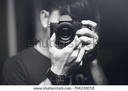 hipster image. a man use camera for taking himself in the mirror. male photographer taking a picture with camera. black and white picture style. selective focus