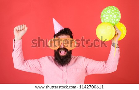 Hipster in giant sunglasses celebrating birthday. Celebration concept. Guy in party hat celebrates holiday. Man with beard and mustache on happy face holds bunch of air balloons, red background.