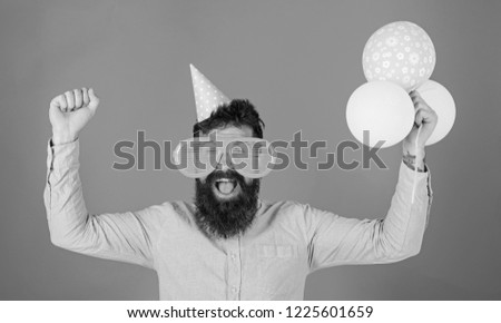 Hipster in giant sunglasses celebrating birthday. Celebration concept. Guy in party hat celebrates holiday. Man with beard and mustache on happy face holds bunch of air balloons, red background. #1225601659