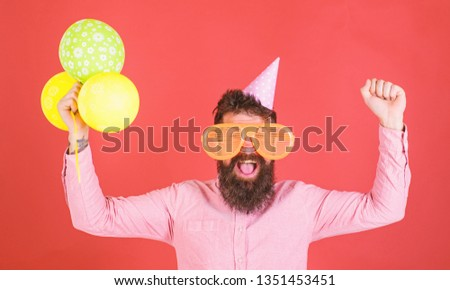 Hipster in giant sunglasses celebrating birthday. Celebration concept. Guy in party hat celebrates holiday. Man with beard and mustache on happy face holds bunch of air balloons, red background. #1351453451