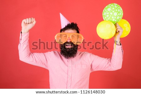 Hipster in giant sunglasses celebrating birthday. Guy in party hat celebrates holiday. Celebration concept. Man with beard and mustache on happy face holds bunch of air balloons, red background. #1126148030