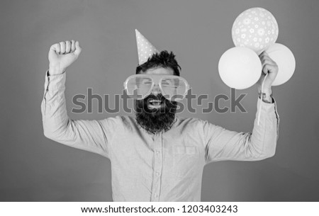 Hipster in giant sunglasses celebrating birthday. Guy in party hat celebrates holiday. Celebration concept. Man with beard and mustache on happy face holds bunch of air balloons, red background.