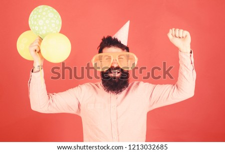 Hipster in giant sunglasses celebrating birthday. Guy in party hat celebrates holiday. Celebration concept. Man with beard and mustache on happy face holds bunch of air balloons, red background. #1213032685