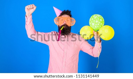 Hipster in giant sunglasses celebrating birthday. Man with beard and mustache on happy face blows into party horn, blue background. Celebration concept. Guy in party hat with air balloons celebrates. #1131141449