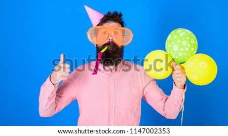 Hipster in giant sunglasses celebrating birthday. Man with beard and mustache on happy face blows into party horn, blue background. Guy in party hat with air balloons celebrates. Celebration concept.