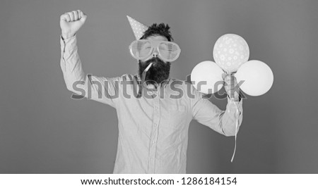 Hipster in giant sunglasses celebrating birthday. Man with beard and mustache on happy face blows into party horn, blue background. Celebration concept. Guy in party hat with air balloons celebrates. #1286184154