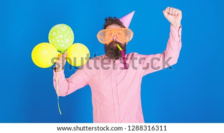 Hipster in giant sunglasses celebrating birthday. Man with beard and mustache on happy face blows into party horn, blue background. Celebration concept. Guy in party hat with air balloons celebrates. #1288316311