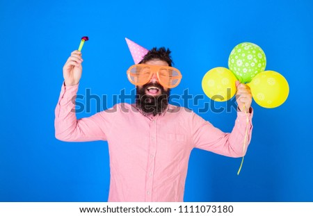Hipster in giant sunglasses celebrating birthday. Man with beard and mustache on happy face holds party horn, blue background. Celebration concept. Guy in party hat with air balloons celebrates. #1111073180