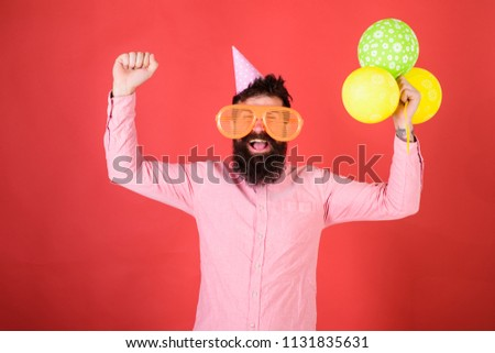 Hipster in giant sunglasses celebrating birthday. Man with beard and mustache on happy face holds bunch of air balloons, red background. Guy in party hat celebrates holiday. Celebration concept.