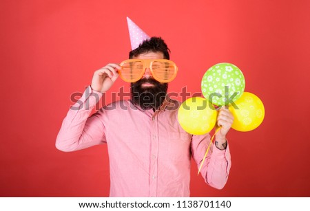 Hipster in giant sunglasses celebrating birthday. Man with beard and mustache on happy face holds bunch of air balloons, red background. Celebration concept. Guy in party hat celebrates holiday.