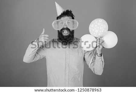 Hipster in giant sunglasses celebrating birthday. Man with beard and mustache on happy face holds bunch of air balloons, red background. Celebration concept. Guy in party hat shows thumb up gesture. #1250878963