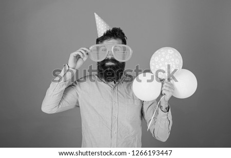 Hipster in giant sunglasses celebrating birthday. Man with beard and mustache on happy face holds bunch of air balloons, red background. Celebration concept. Guy in party hat celebrates holiday. #1266193447