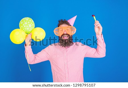Hipster in giant sunglasses celebrating birthday. Man with beard and mustache on happy face holds party horn, blue background. Celebration concept. Guy in party hat with air balloons celebrates. #1298795107