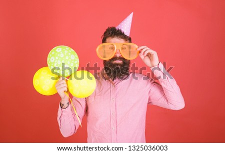 Hipster in giant sunglasses celebrating birthday. Man with beard and mustache on happy face holds bunch of air balloons, red background. Celebration concept. Guy in party hat celebrates holiday. #1325036003