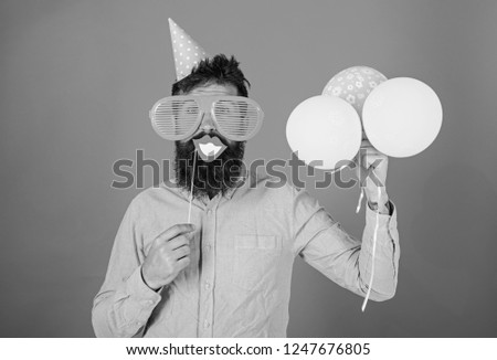 Hipster in giant sunglasses celebrating. Guy in party hat with air balloons celebrates. Man with beard on cheerful face holds smiling mouth on stick, red background. Photo booth fun concept. #1247676805