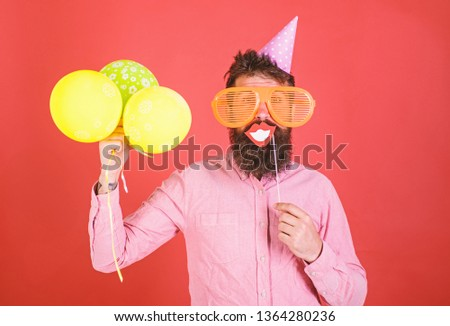 Hipster in giant sunglasses celebrating. Guy in party hat with air balloons celebrates. Man with beard on cheerful face holds smiling mouth on stick, red background. Photo booth fun concept. #1364280236