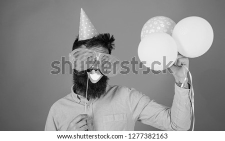 Hipster in giant sunglasses celebrating. Man with beard on cheerful face holds smiling mouth on stick, red background. Guy in party hat with air balloons celebrates. Photo booth fun concept.