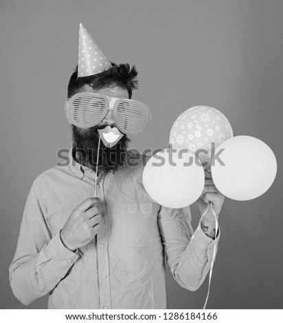 Hipster in giant sunglasses celebrating. Man with beard on cheerful face holds smiling mouth on stick, red background. Photo booth fun concept. Guy in party hat with air balloons celebrates.