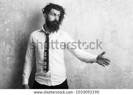 Hipster in shirt and musical tie. Man with long beard and mustache on face. Fashion model with stylish hair on textured wall background Guy hold hand for handshake. Business fashion and beauty. #1033092190