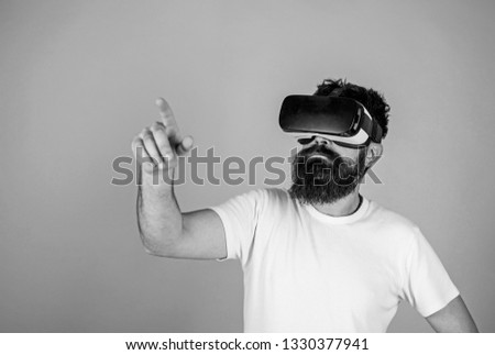 Hipster in VR glasses checks new device, modern technology concept. Bearded man absorbed in virtual reality game. Man with nerdy beard using digital touch screen interface isolated on blue background.
