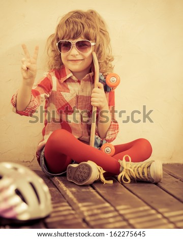 Hipster kid holding skateboard in hands