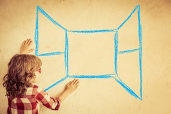 Hipster kid looking out of the drawn open window on grunge wall. Freedom concept
