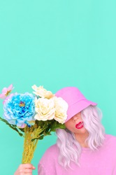Hipster Lady with flowers in trendy bucket hat. Fresh summer vibes. Pastel colours lovers