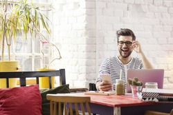Hipster laughing while browsing social media on the phone in raw interior