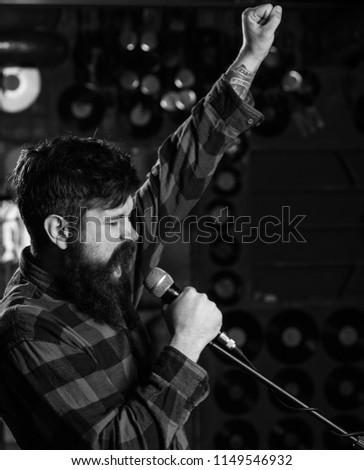 Hipster likes to sing on stage. Man with enthusiastic face holds microphone, singing song, karaoke club background. Music and leisure concept. Musician with beard and mustache singing song in karaoke. #1149546932