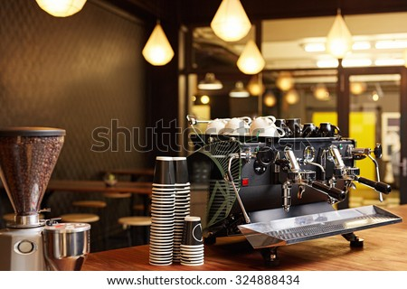 Hipster looking coffee shop ready to open for the day with a clean and tidy counter and well-maintained shiny coffee machine on the the wooden surface