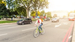 Hipster man cycling in London on a busy street. He is riding a fixed gear bike and wearing a helmet. Panning technique to blur cars and background. Transportation and lifestyle concepts.