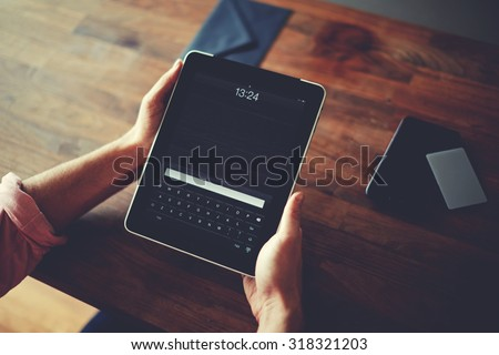 Hipster man hands holding digital tablet with empty blank screen for your text message, business person browsing internet or connecting to wireless via touchscreen pad sitting at brown wooden table