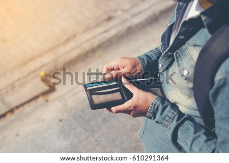 Hipster man hands holding wallet with credit cards and stack of money. - Shutterstock ID 610291364
