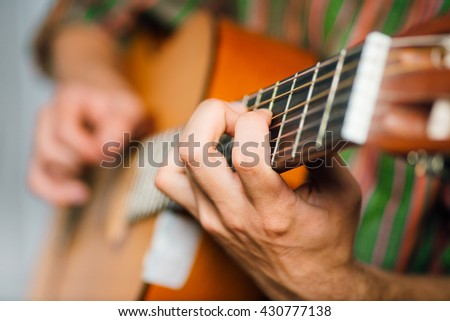 hipster man playing classical guitar, wears a hat and glasses, isolated on a gray background