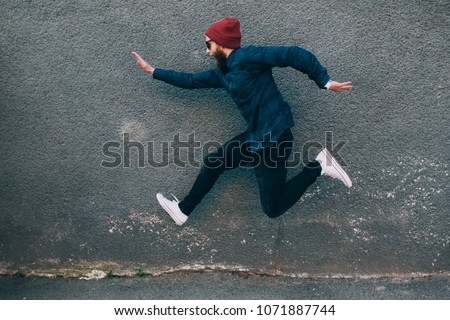 hipster man runs in the air along an empty wall. Crazy emotions. Fashionable guy with a beard #1071887744