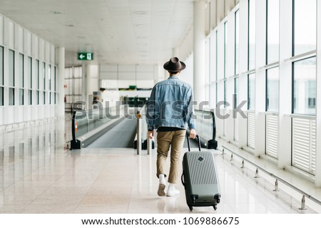 hipster man traveler tourist in a hat, white shoes and jeans jacket with luggage walking in an empty airport departure area. Male person with a suitcase going to holidays
