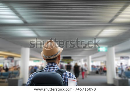 Hipster man walking in passenger terminal building  of the airport  calling on board ,travel concept.Travel. #745715098
