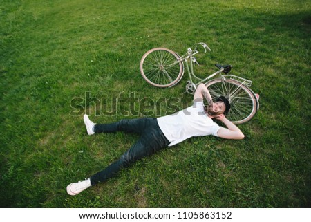 Hipster man with beard relaxing next to a bike and smiling/ He is wearing white t-shirt and black jeans and a black snap back cap