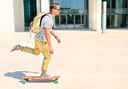 Hipster men going to  study in city with an alternative and ecologic way. Concept of carefree youth and freedom outdoors against city background. Active guy enjoying everyday life moments doing sport