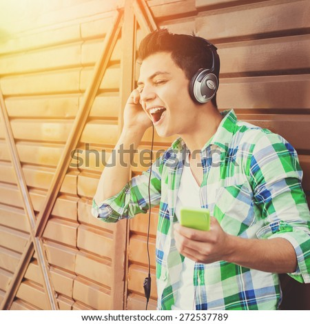 Hipster mixed race young man singing. Closeup of handsome guy with headphones and smartphone in green plaid shirt listening to music. Natural light, retouched, filter applied, square format.